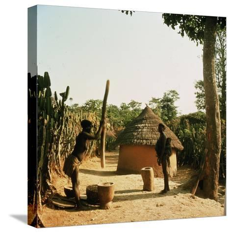 A Woman Grinding Millet with a Pestle and Mortar in a Miango Village Near Jos--Stretched Canvas Print