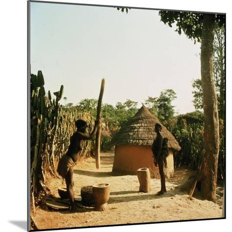 A Woman Grinding Millet with a Pestle and Mortar in a Miango Village Near Jos--Mounted Giclee Print