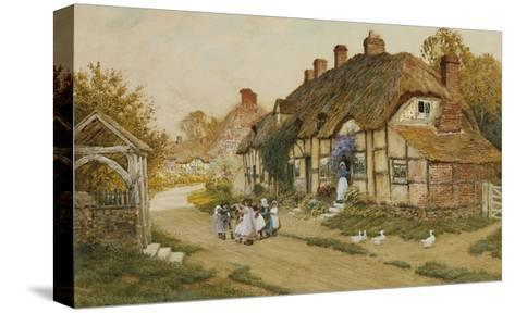 Children Playing Outside a Cottage in a Village-Arthur Claude Strachan-Stretched Canvas Print