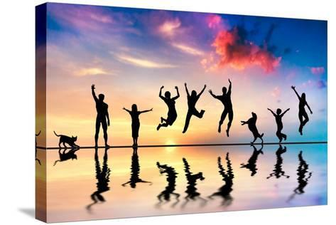 Happy Group Of Friends, Family With Dog And Cat Jumping Together At Sunset, Water Reflection-Michal Bednarek-Stretched Canvas Print