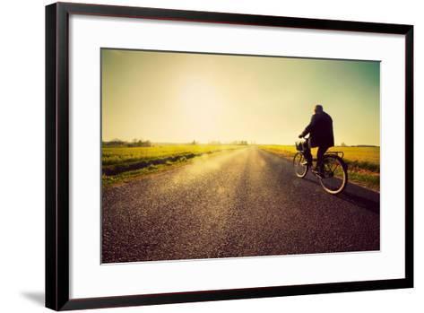 Old Man Riding A Bike On Asphalt Road Towards The Sunny Sunset Sky-Michal Bednarek-Framed Art Print