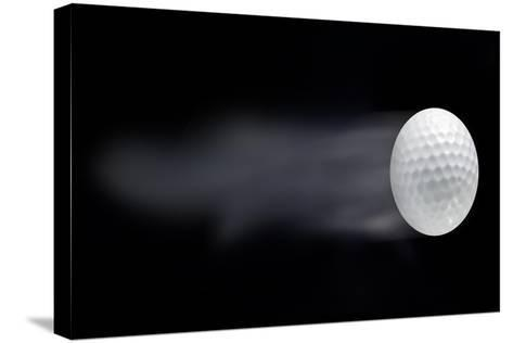 Golf Ball Leaving Trails Behind On Black Background--Stretched Canvas Print