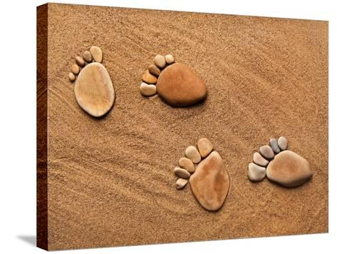 Trace Feet Steps Made Of A Pebble Stone On The Sea Sand Backdrop-Madlen-Stretched Canvas Print