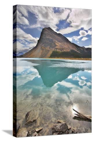 The Huge Rock Of The Triangular Form Is Reflected In Emerald Waters Of Cold Mountain Lake-kavram-Stretched Canvas Print