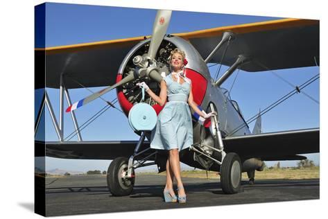 Elegant 1940's Style Pin-Up Girl Standing in Front of an F3F Biplane--Stretched Canvas Print