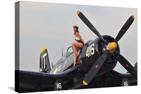 1940's Style Navy Pin-Up Girl Sitting on a Vintage Corsair Fighter Plane--Stretched Canvas Print