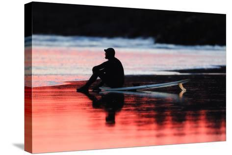 A Surfer Sits on His Surfboard While Watching the Waves at Sunset-Robbie George-Stretched Canvas Print