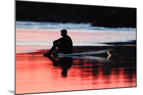 A Surfer Sits on His Surfboard While Watching the Waves at Sunset-Robbie George-Mounted Photographic Print