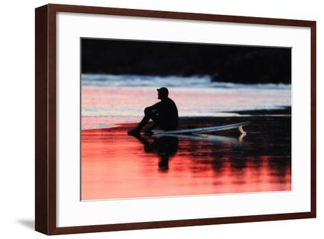 A Surfer Sits on His Surfboard While Watching the Waves at Sunset-Robbie George-Framed Art Print