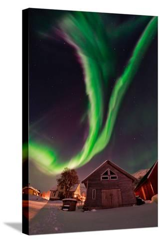 The Aurora Borealis, or Northern Lights, Appear Above a Village-Babak Tafreshi-Stretched Canvas Print