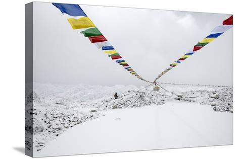 A Porter Walks by a Puja with Prayer Flag in Everest Base Camp, Nepal-Alex Treadway-Stretched Canvas Print