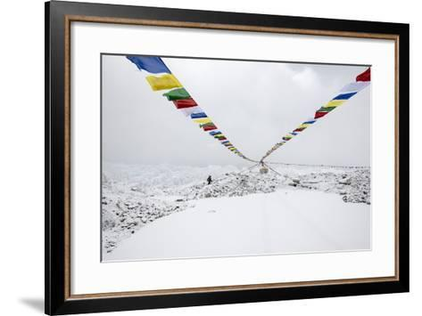 A Porter Walks by a Puja with Prayer Flag in Everest Base Camp, Nepal-Alex Treadway-Framed Art Print