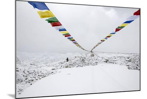 A Porter Walks by a Puja with Prayer Flag in Everest Base Camp, Nepal-Alex Treadway-Mounted Photographic Print