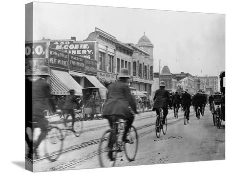 Los Angeles Police Officers Bicycling Past Broadway Storefronts--Stretched Canvas Print