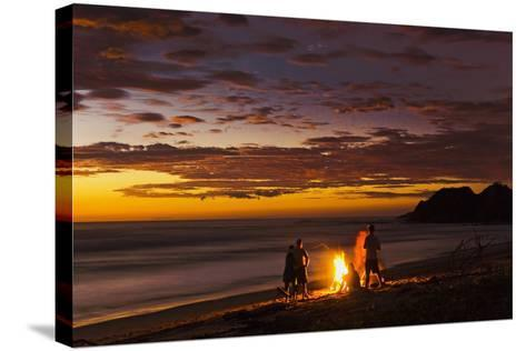 People with Driftwood Fire at Sunset on Playa Guiones Beach-Rob Francis-Stretched Canvas Print