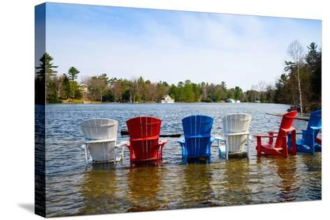 Adirondack Chairs Partially Submerged in the Lake Muskoka, Ontario, Canada--Stretched Canvas Print