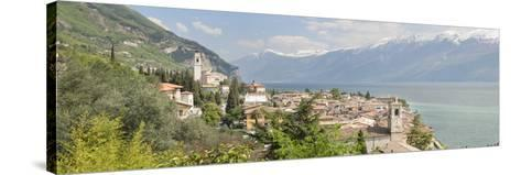 Buildings at the Waterfront with Snowcapped Mountain in the Background, Gargnano, Monte Baldo--Stretched Canvas Print