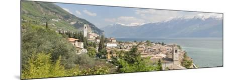 Buildings at the Waterfront with Snowcapped Mountain in the Background, Gargnano, Monte Baldo--Mounted Photographic Print