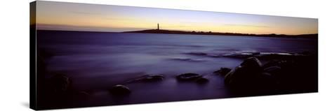 Rock Formations in the Sea with a Lighthouse in the Background, Cape Leeuwin, Western Australia--Stretched Canvas Print