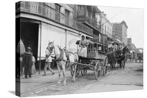 Woman Driving Horse-Drawn Wagon on Street--Stretched Canvas Print