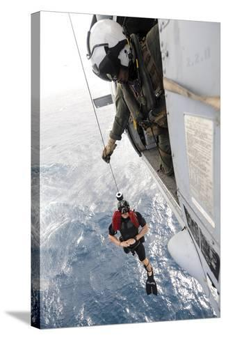 Aircrewman Assists in Hoisting a Member into an Mh-60S Sea Hawk--Stretched Canvas Print