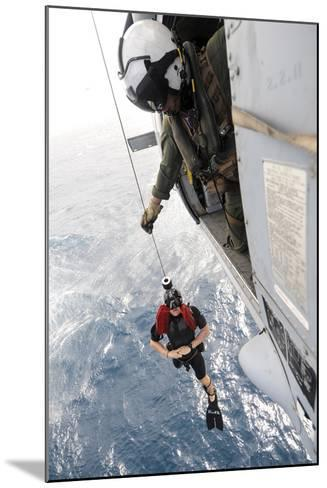 Aircrewman Assists in Hoisting a Member into an Mh-60S Sea Hawk--Mounted Photographic Print