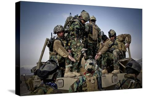 Afghan Soldiers Give a Hand Up to a Fellow Soldier--Stretched Canvas Print