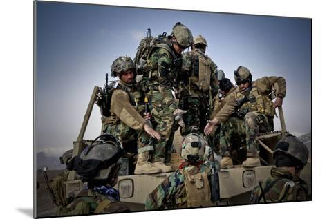 Afghan Soldiers Give a Hand Up to a Fellow Soldier--Mounted Photographic Print