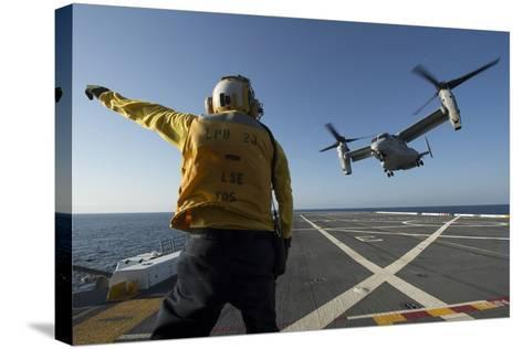 Aviation Boatswain's Mate Directs an MV-22 Osprey as it Launches from the Flight Deck--Stretched Canvas Print