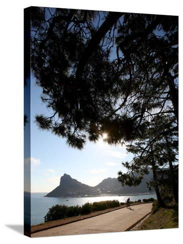 A Cyclist Rides Past the Sentinel Peak in Hout Bay Near Cape Town, South Africa-Jon Hrusa-Stretched Canvas Print