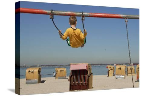 A Boy Plays on a Swing at the Beach of Laboe, Germany-Christian Hager-Stretched Canvas Print