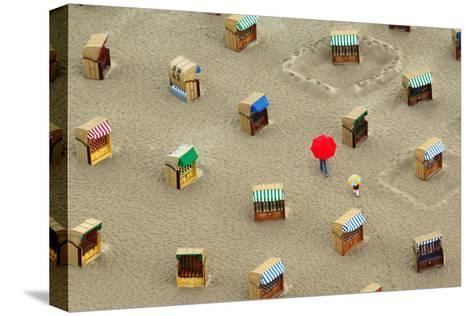 Two Strollers Walk with Umbrellas Between Beach Chairs at the Beach of Travemuende-Wolfgang Langenstrassen-Stretched Canvas Print