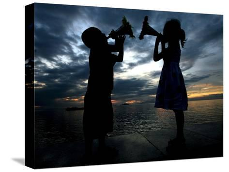 Two Children Sound their Toy Trumpets Along the Manila Baywalk in Manila, Philippines-Mike F. Alquinto-Stretched Canvas Print
