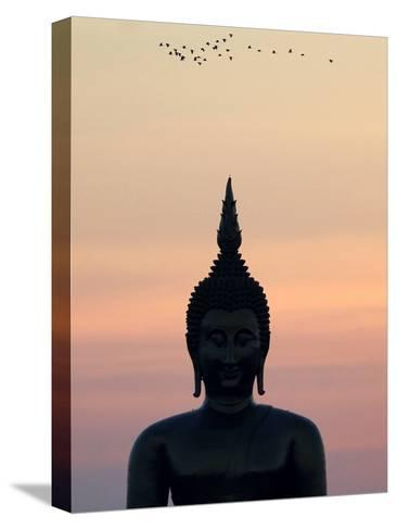 Birds Fly Past the Head of a Giant Buddha at Wat Muang-Barbara Walton-Stretched Canvas Print
