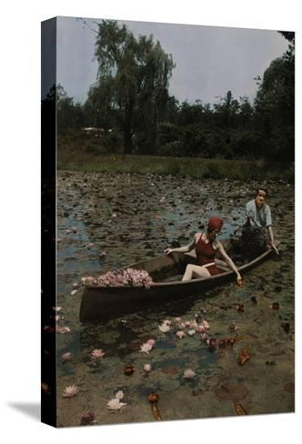 A Couple in a Boat Paddle on a Lily Pond and Collect Flowers-Charles Martin-Stretched Canvas Print