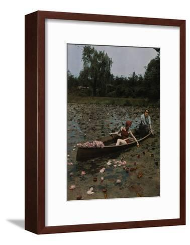 A Couple in a Boat Paddle on a Lily Pond and Collect Flowers-Charles Martin-Framed Art Print