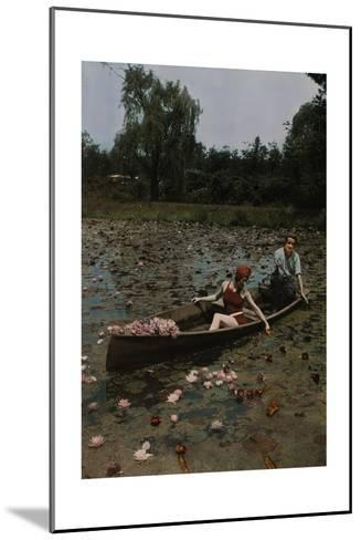 A Couple in a Boat Paddle on a Lily Pond and Collect Flowers-Charles Martin-Mounted Photographic Print
