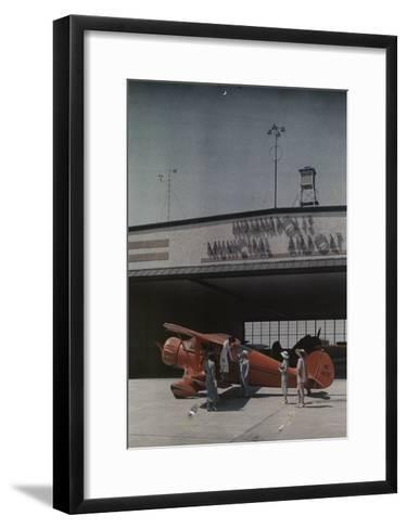 A Woman Exits a Plane with Help While Other People Watch-Willard Culver-Framed Art Print