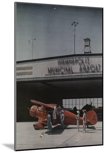 A Woman Exits a Plane with Help While Other People Watch-Willard Culver-Mounted Photographic Print