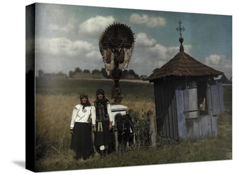 Two Women Stand Beside a Roadside Shrine-Hans Hildenbrand-Stretched Canvas Print