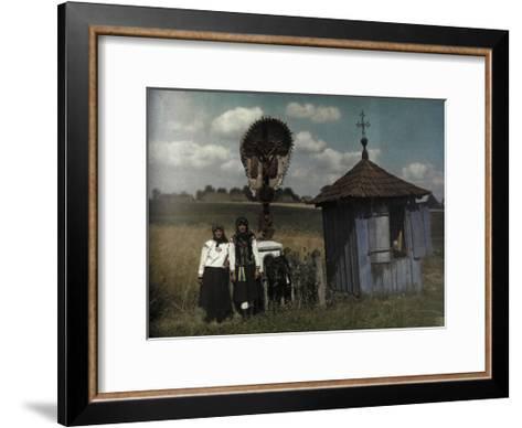 Two Women Stand Beside a Roadside Shrine-Hans Hildenbrand-Framed Art Print
