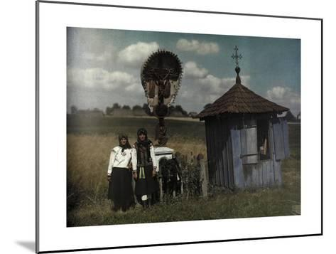 Two Women Stand Beside a Roadside Shrine-Hans Hildenbrand-Mounted Photographic Print