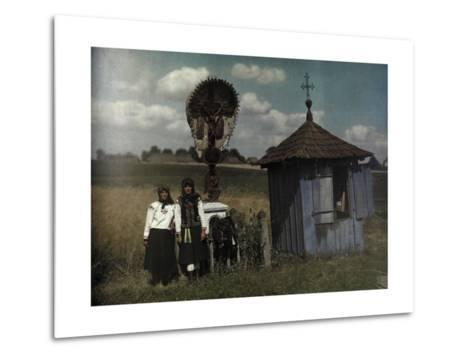 Two Women Stand Beside a Roadside Shrine-Hans Hildenbrand-Metal Print