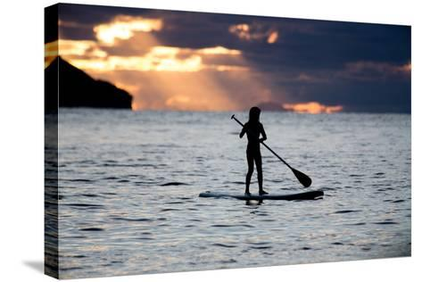 A Young Girl on a Stand Up Paddle Board on Baleia Beach at Sunset-Alex Saberi-Stretched Canvas Print