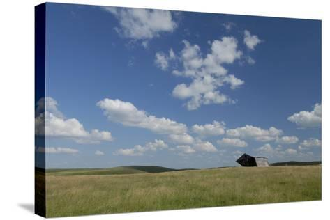 An Abandoned Barn in a Vast Field under a Sky with Puffy Clouds-Michael Forsberg-Stretched Canvas Print