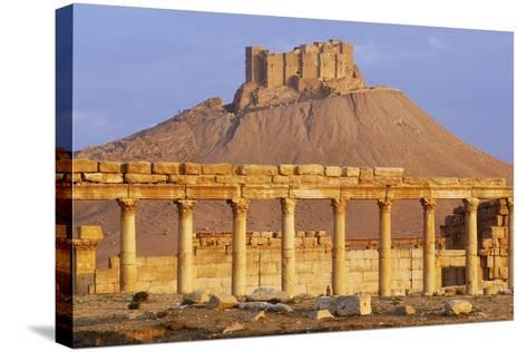 Syria, Palmyra, Column Ruins with Qalaat Ibn Maan Castle in Background--Stretched Canvas Print