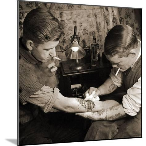 Vintage Shot of a Man Being Tattooed--Mounted Photographic Print