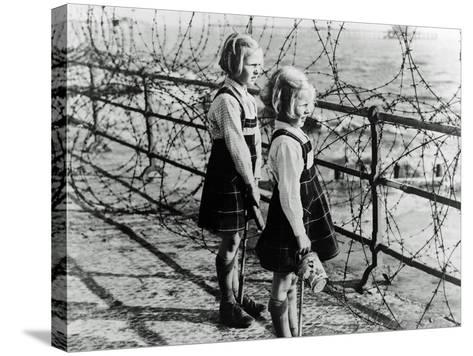 Two Girls on the South Coast of England Look Out Toward the Beach Through a Barbed Wire Fence--Stretched Canvas Print
