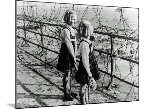 Two Girls on the South Coast of England Look Out Toward the Beach Through a Barbed Wire Fence--Mounted Photographic Print