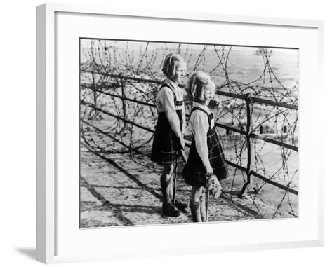 Two Girls on the South Coast of England Look Out Toward the Beach Through a Barbed Wire Fence--Framed Art Print
